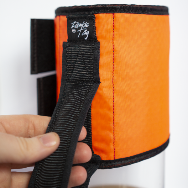 orange ramble tag with black rim. a hand is holding the handle to show scale