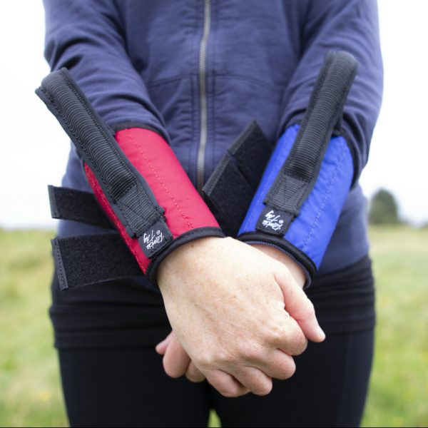guide wearing a small ramble tag on each wrist for guide running, or guiding a child. red and blue in this picture, they have a black rim and black handle.