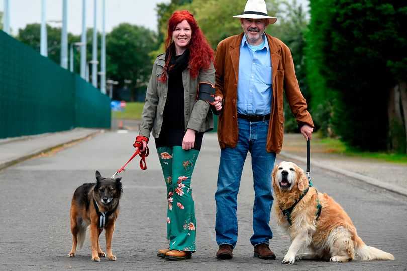 Tom and Laura with their dogs using a ramble tag on Lauras arm, while Tom who is blind holds the handle.