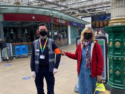blind lady and her guide dog being guided by train staff using a ramble tag. they are in a train station